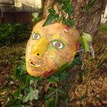 Mask And Ivy On Tree Trunk